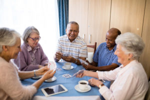 senior friends playing cards at table