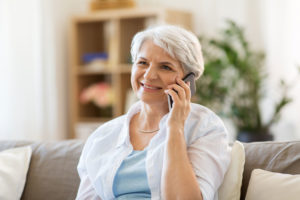 happy senior woman calling on smartphone at home