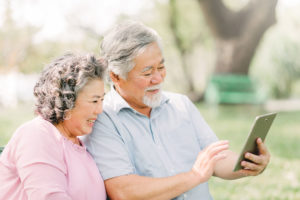 happy senior couple using tablet