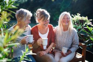 Senior women friends with coffee sitting outdoors on terrace